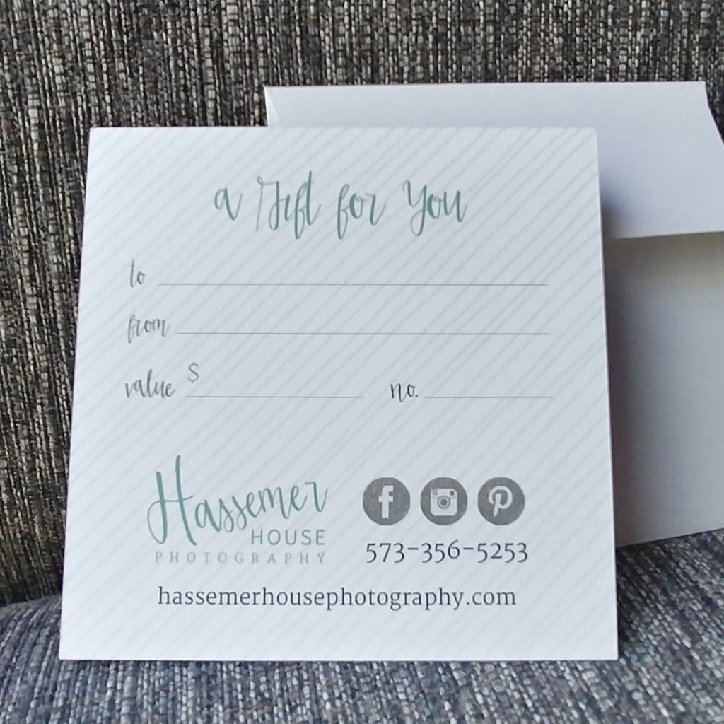 A square gift certificate leans against a white envelop on a heathered grey textured backdrop.