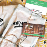 Evolve Grass Roots Naturals business card is tucked under a twine wrapping a package. The back of the business card is seen under the packages.