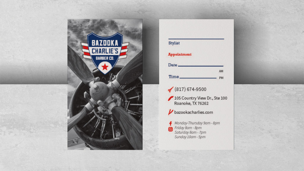 Vertical business cards lay flat across the edge of a light grey background. The left card has a photograph of a black and white plan propeller with a red, white, and blue Bazooka Charlie's Barber Co. logo on the top third. The right card is implied to be the other side and lists contact information as well as blanks for filling in future appointments.